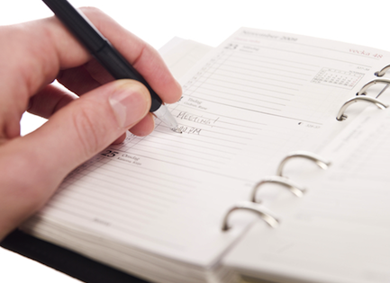Person making a notation in a personal calendar