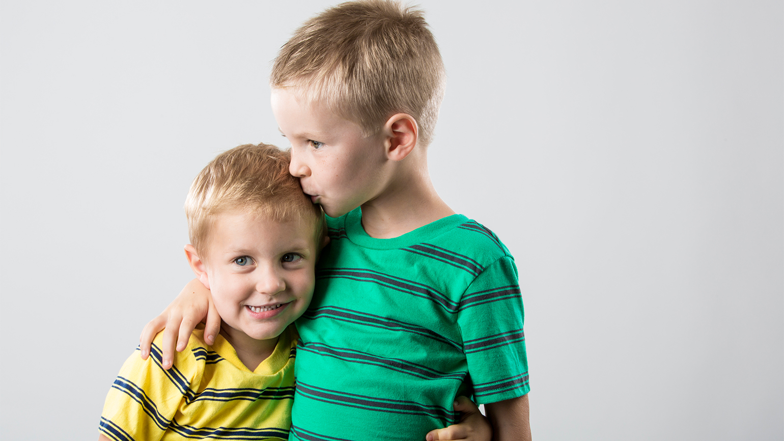 A boy hugs his younger brother in forgiveness