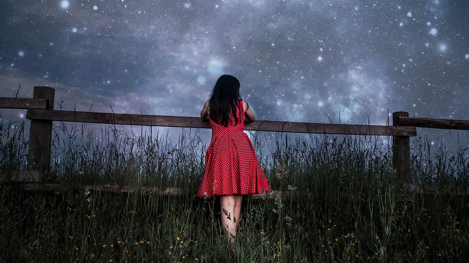 A young woman gazes up at a star-filled sky