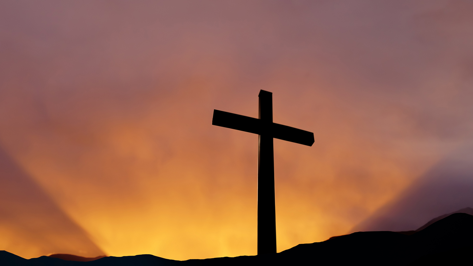 The empty cross stands tall in the face of the sunrise