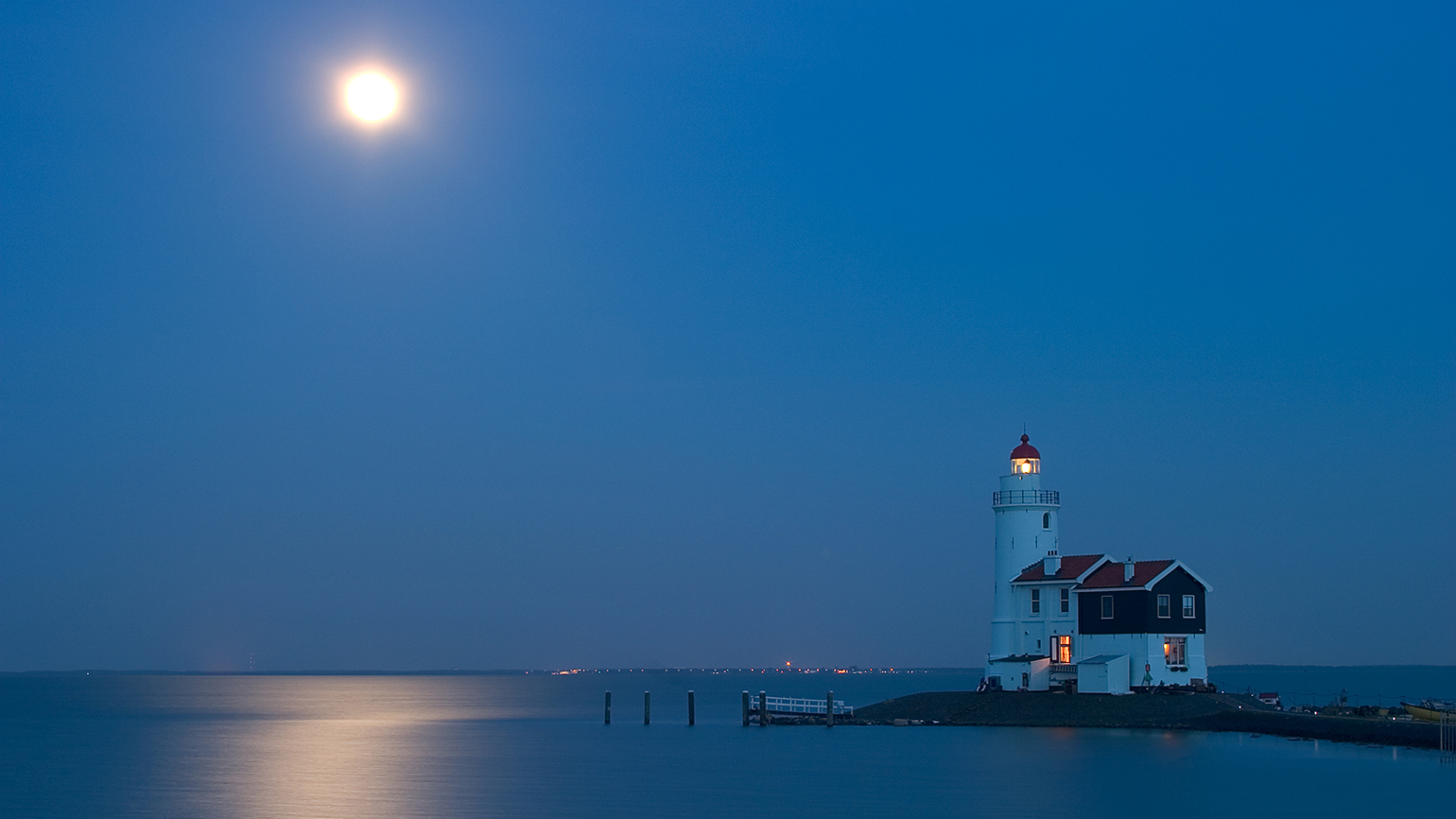 A lighthouse towers over a moonlit bay