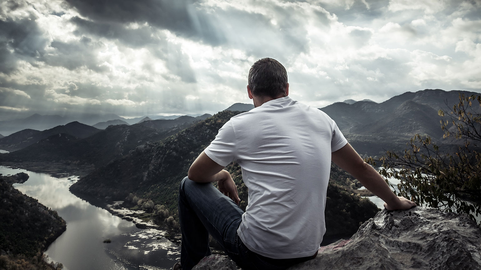 A man gazes out at sunbeams shining down on mountains