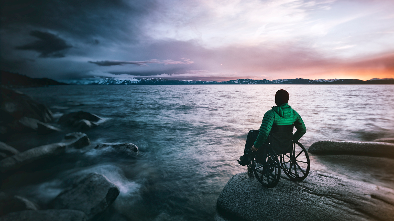 A man in a wheelchair looks out at the ocean from a rocky beach