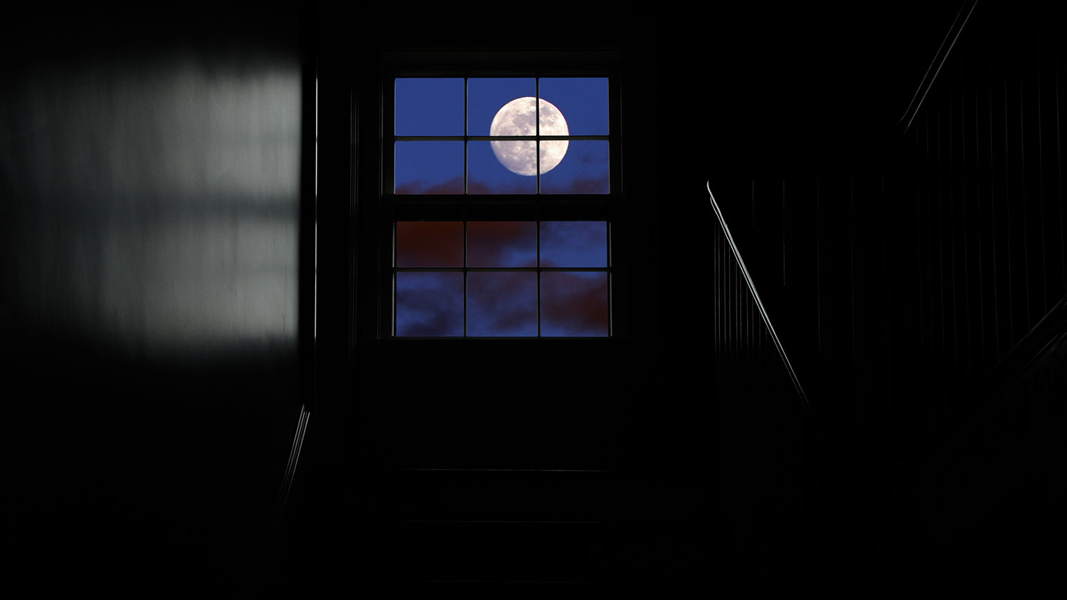 The moon as seen out a window at the top of a darkened staircase