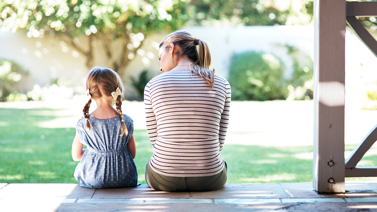 A mother talks with her young daughter while sitting on a porch