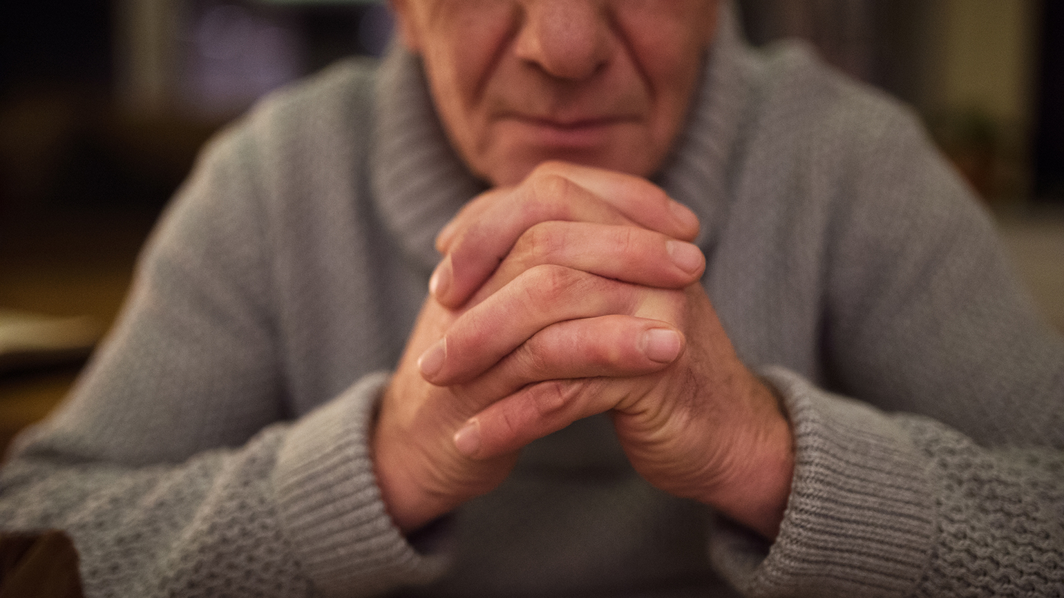 A senior man clasps his hands in prayer