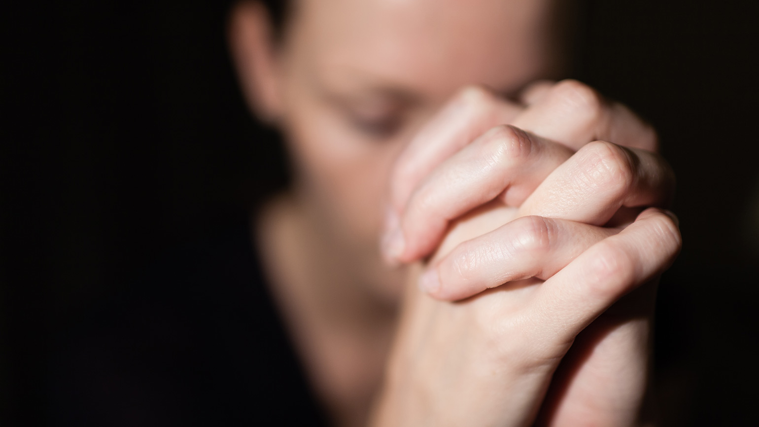 A woman clasps her hands in prayer