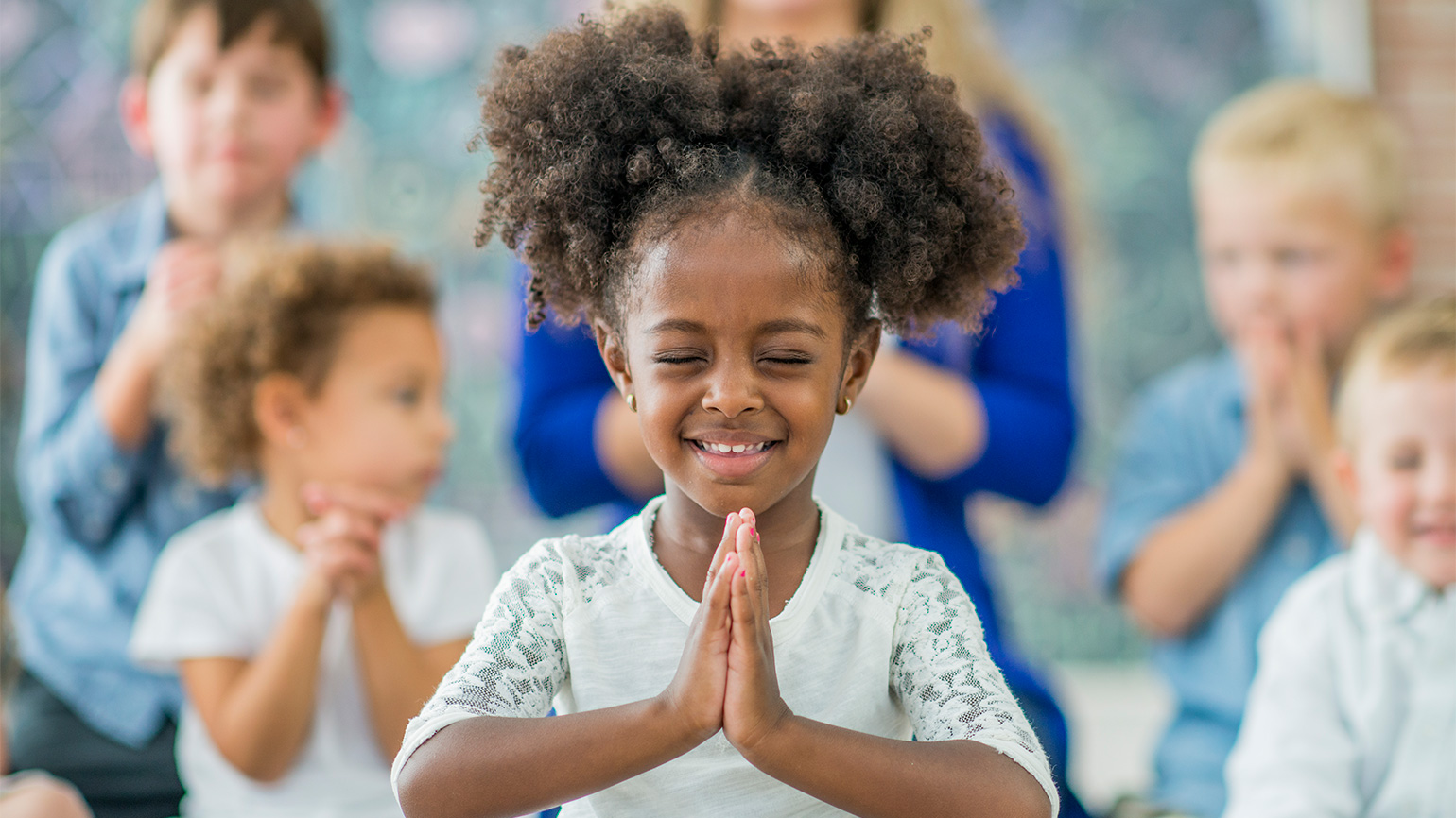 A young girl smiles as she prays