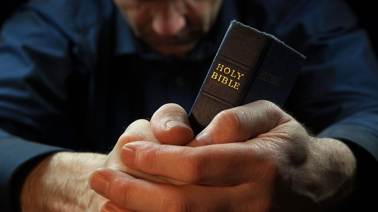 A man prays as his hands clasp a Bible