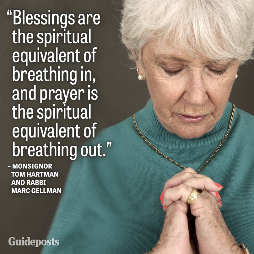 A woman bows her head in prayer.