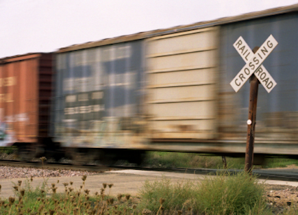 Boxcars traveling through a railroad crossing.