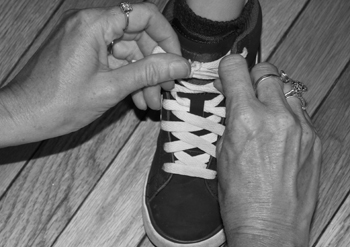 A mother's hands tying a young boy's shoelaces