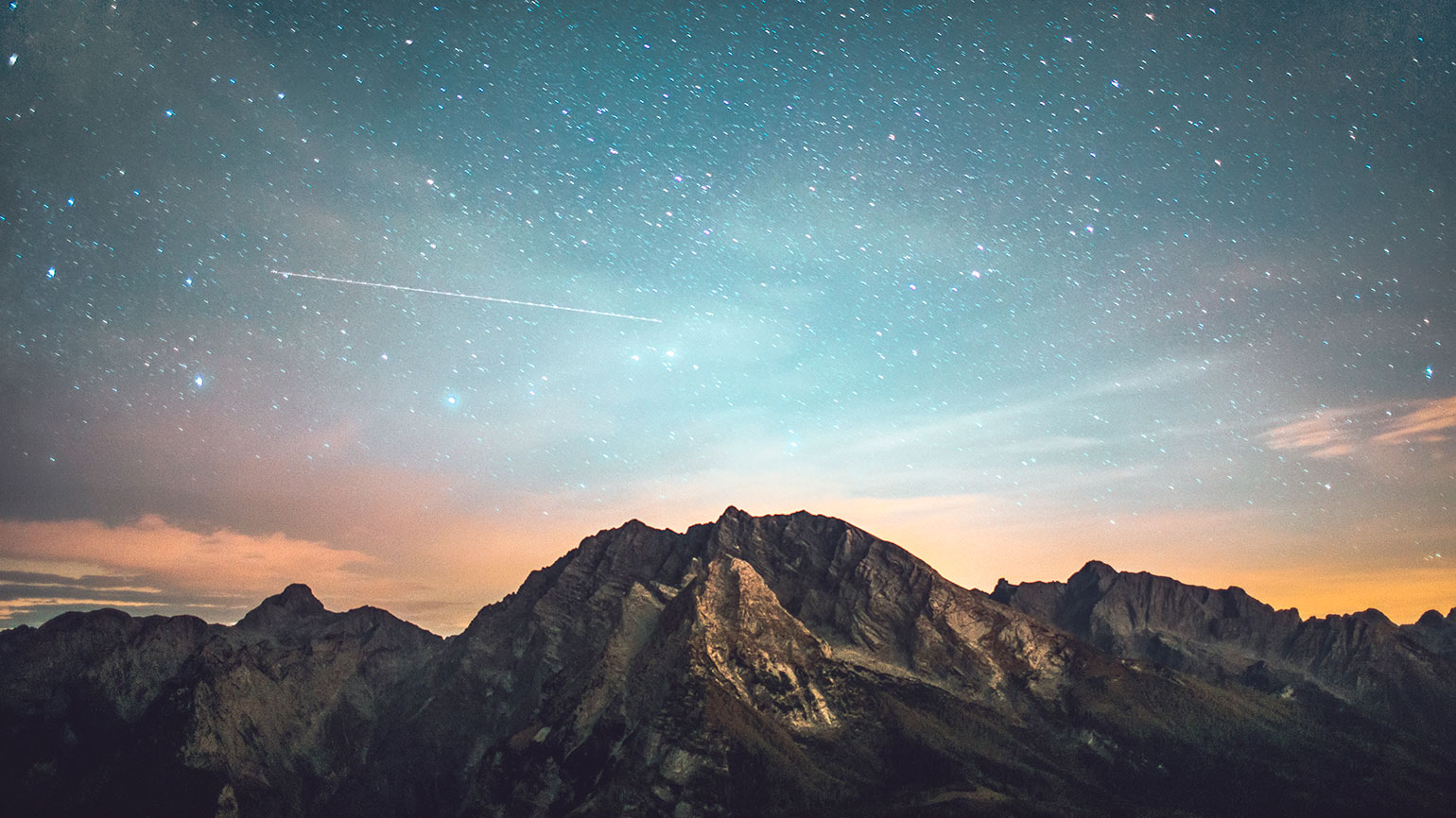 A starlit early-evening sky over a mountain
