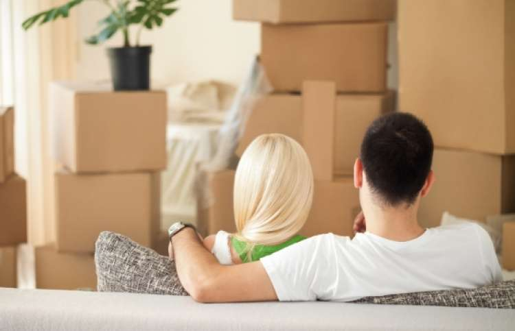 A couple looking at moving boxes in their new apartment.