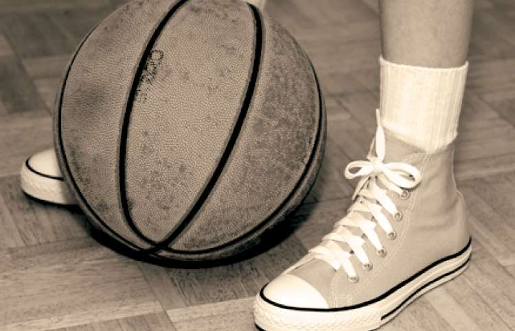 A sepia photo of a weathered basketball and a pair of feet in high-tops