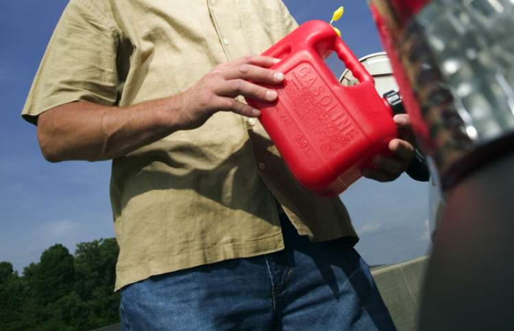 A man uses a gas can to fill a car's empty gas tank.