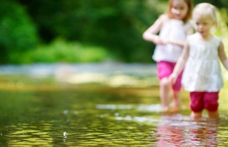 two little girls playing in a creek