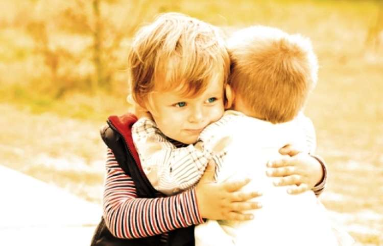 two adorable toddlers embracing