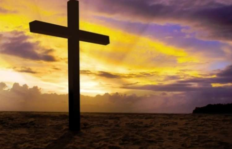 Cross in a beautiful sunset of yellow and purple.