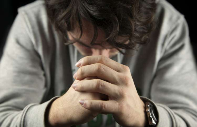 A man bowing his head in prayer