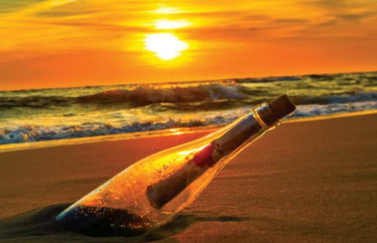A message in a bottle stuck in the sand near the ocean