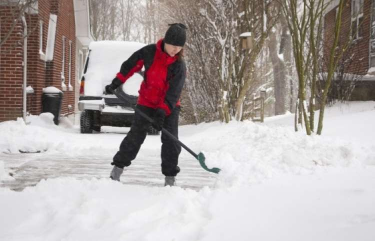 Person shoveling driveway to help a neighbor in need.