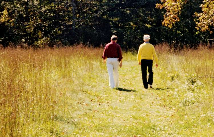 Grant (left) and his father stroll together through a sun-drenched meadow.