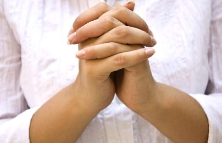 woman's hands clasped in prayer.