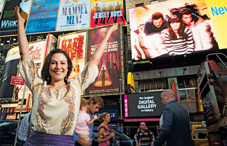 Renee Heitmann with arms aloft in Times Square