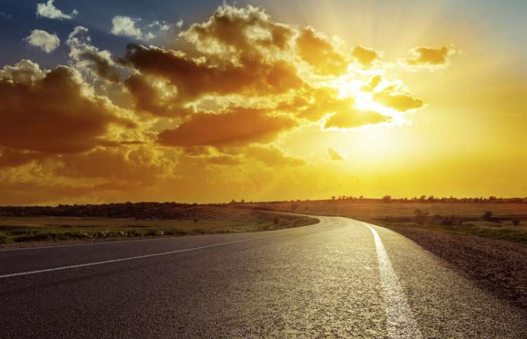 Heavenly beams shine down through the clouds on a curving highway.