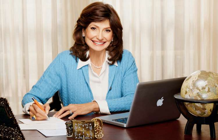 Martha Williamson sits at her desk, smiling as she writes a letter.