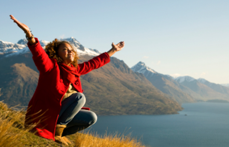 woman on mountain top with arms outstretched in praise
