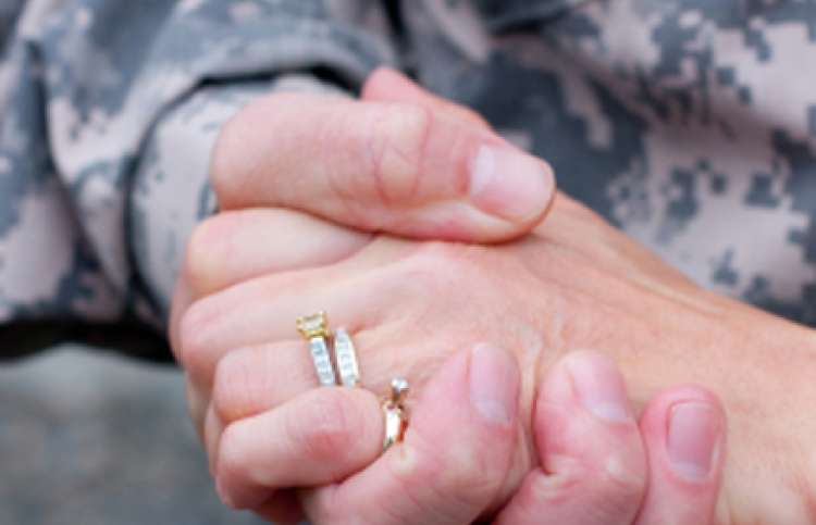 soldier's hand holding onto a hand with wedding ring