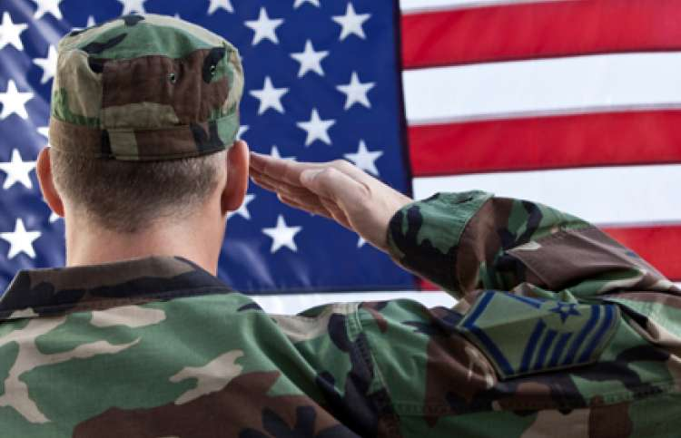 A soldier in fatigues salutes the flag.