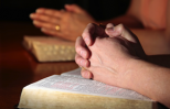 Hands in prayer resting on a Bible