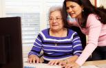 Young woman helps elderly woman on the computer