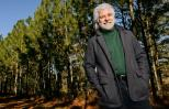 Chuck Leavell poses in front of a long row of his trees.