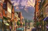 The main street of a small town with a mountain towering in the distance