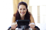 Woman exercising and praying on a stationary bike.