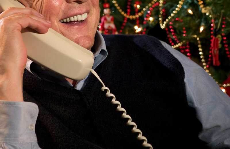 A man takes a Christmas phone call with a smile.