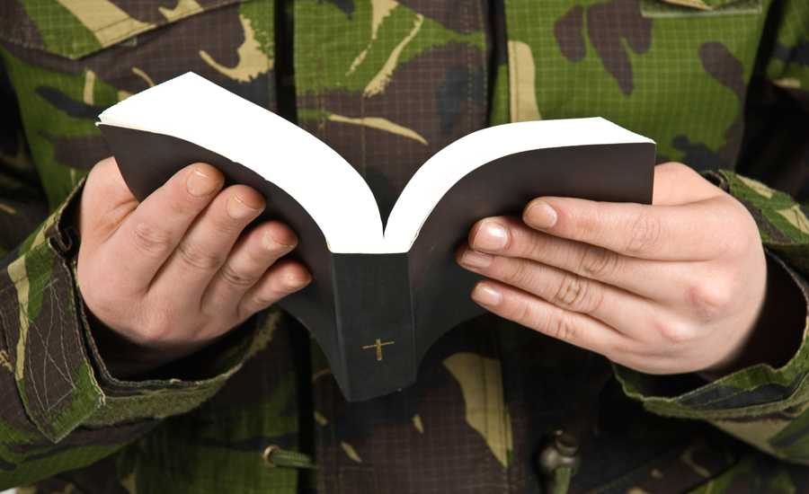 A soldier in camouflage fatigues reads the Holy Bible.