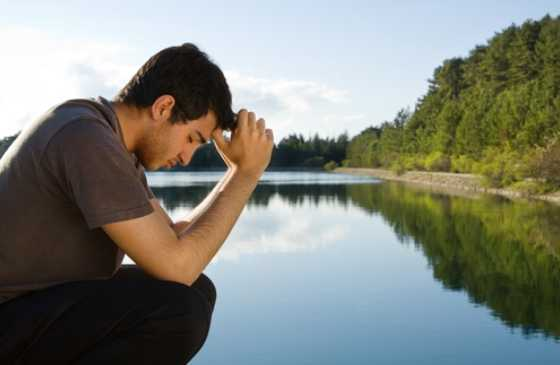 Man praying by a beautiful lake