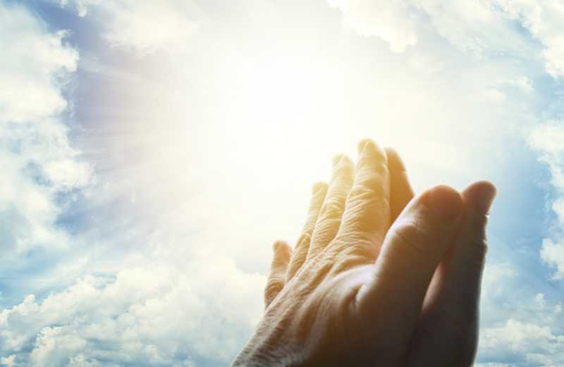 Praying hands lifted to a sunlit sky.