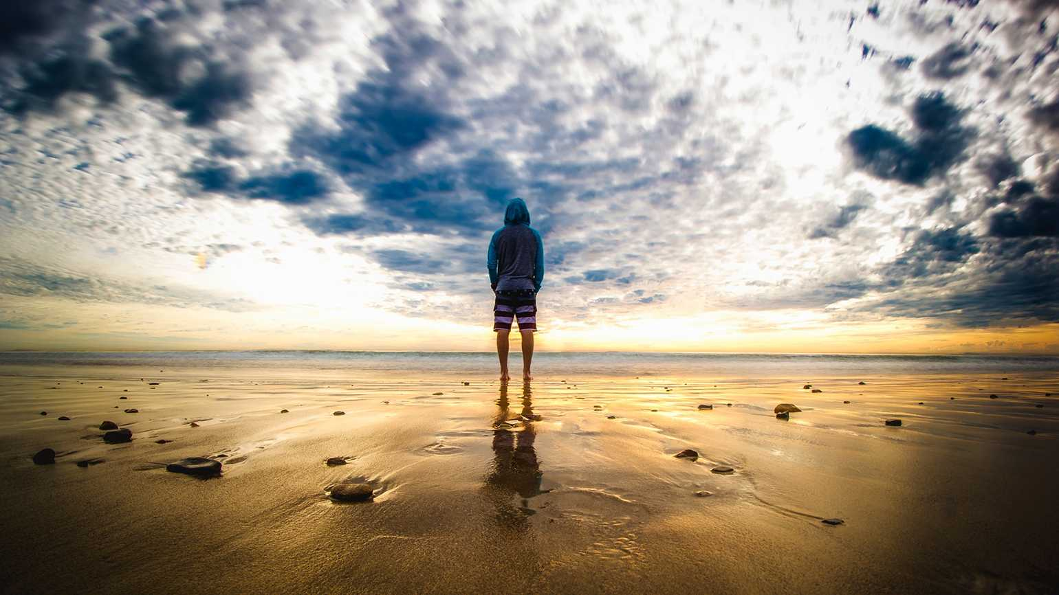 A young man looks out at a sunrise over the ocean