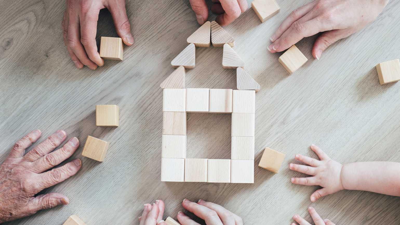 Family members using wooden blocks to form a house.
