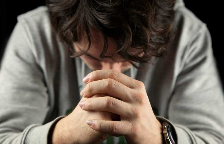 man's hands clasped in prayer as he prays The Lord's Prayer