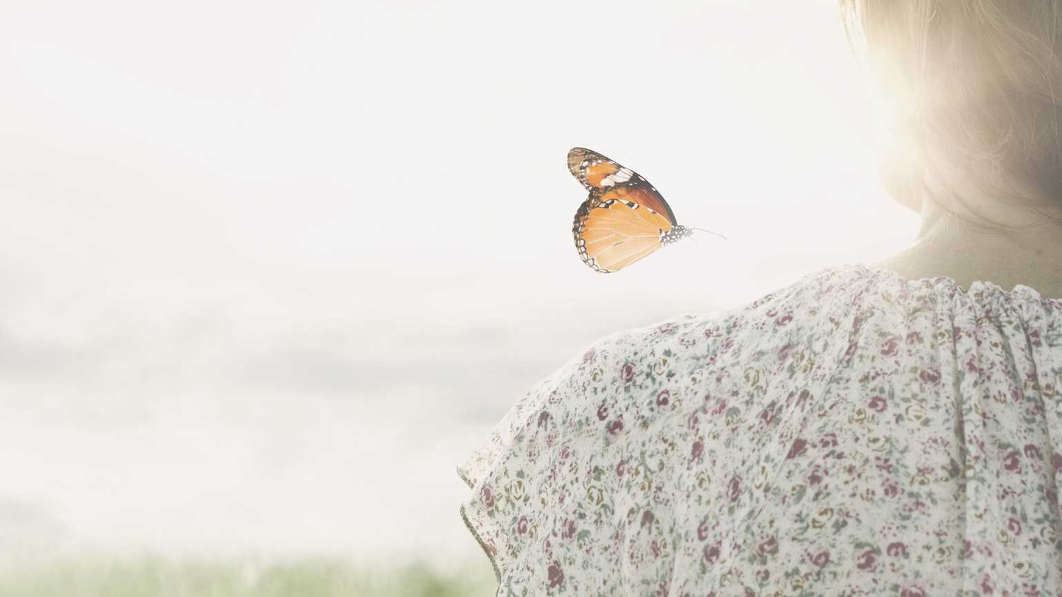A butterfly hovering over a girl's shoulder.