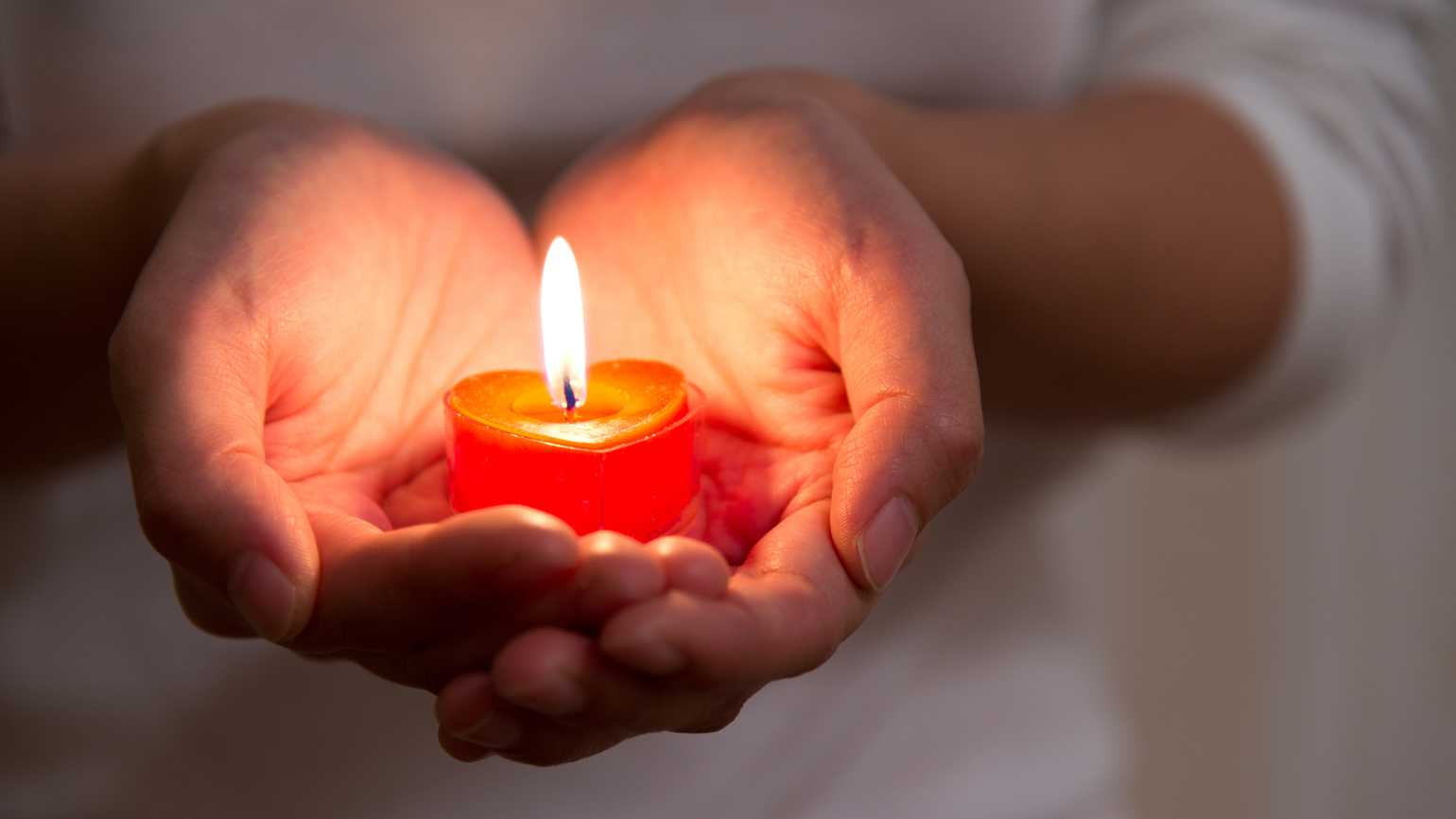 A woman's hands holding a a lit red candle.