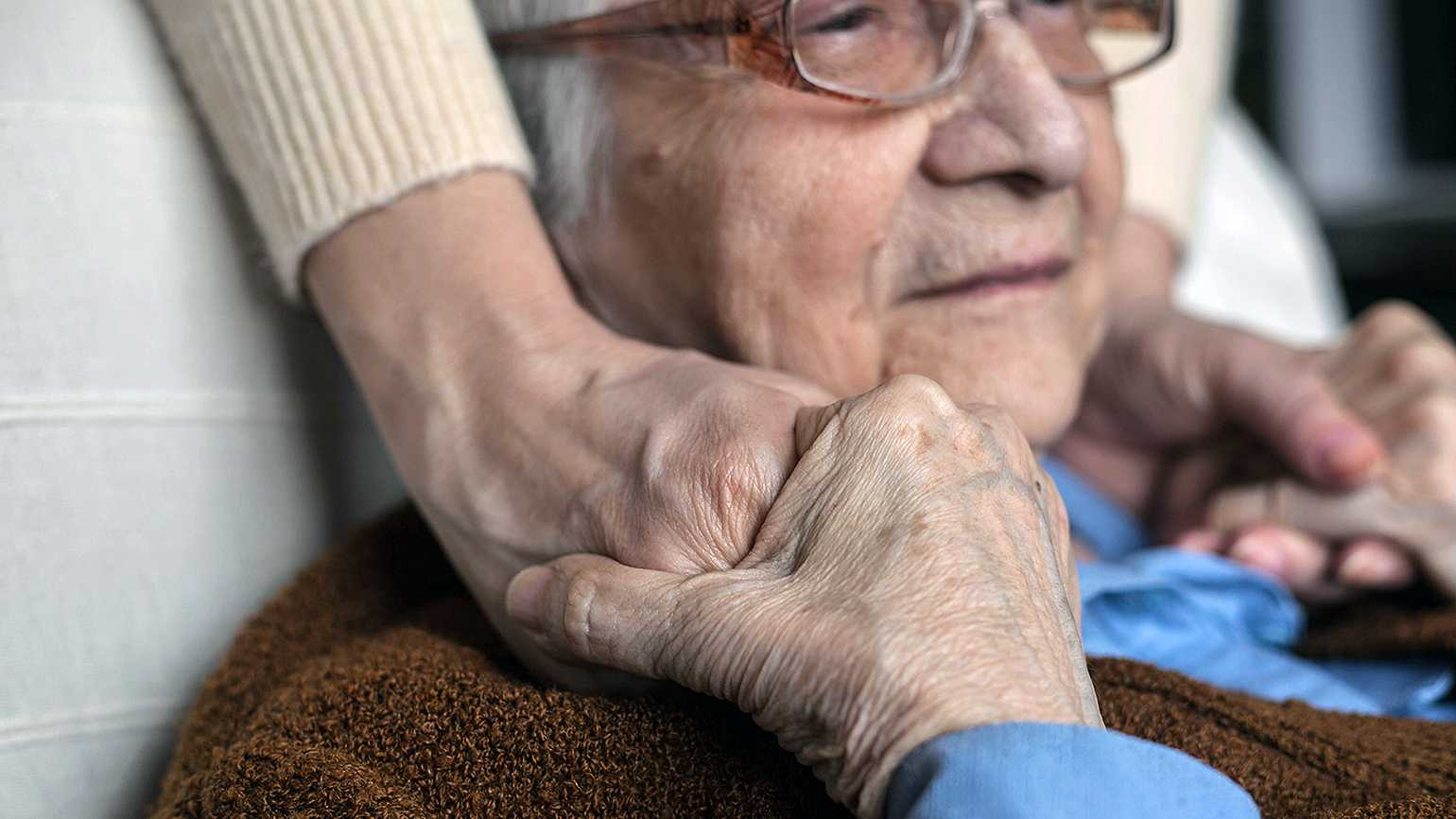 A family member clasps hands with loved one with dementia