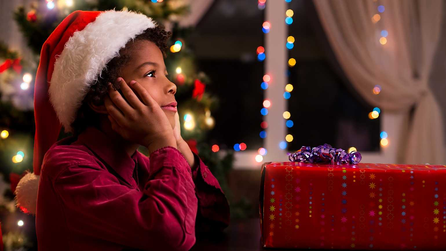 A child in a Santa hat exhibits the wonder of the holidays